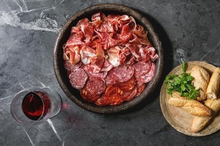 Antipasto meat platter assorti of sliced jamon, salami, chorizo sausage in terracotta tray with bread and glass of red wine over black marble background. Flat lay, space