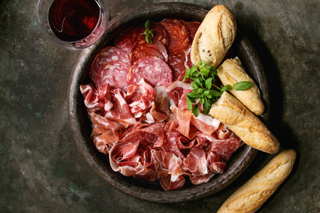 Antipasto meat platter assorti of sliced jamon, salami, chorizo sausage in terracotta tray with bread and glass of red wine over dark metal background. Flat lay, space Banco de Imagens