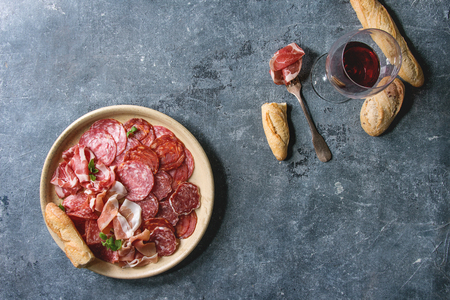 Antipasto meat platter assorti of sliced jamon, salami, chorizo sausage in ceramic plate with bread and glass of red wine over blue texture background. Flat lay, space