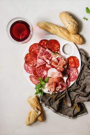 Antipasto meat platter assorti of sliced jamon, salami, chorizo sausage on white ceramic board with bread and glass of red wine on cloth over white marble background. Flat lay, space
