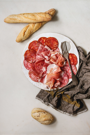 Antipasto meat platter assorti of sliced jamon, salami, chorizo sausage on white ceramic board with bread on cloth over white marble background. Flat lay, space Banco de Imagens
