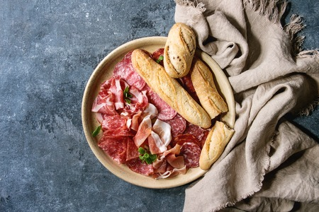 Antipasto meat platter assorti of sliced jamon, salami, chorizo sausage in ceramic plate with bread on cloth over blue texture background. Flat lay, space