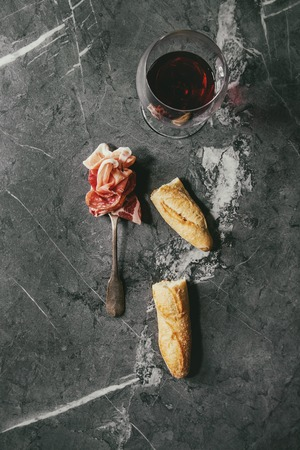 Antipasto meat assorti of sliced jamon, salami, chorizo sausage on fork with bread and glass of red wine over black marble background. Flat lay, space. Appetizer concept