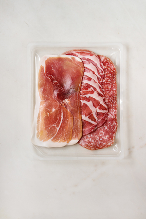 Antipasto meat platter assorti of sliced jamon, salami sausage in opened plastic packaging over white marble background. Flat lay, space