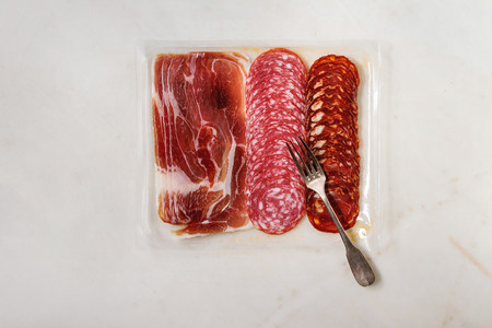 Antipasto meat platter assorti of sliced jamon, salami, chorizo sausage in opened plastic packaging with fork over white marble background. Flat lay, space