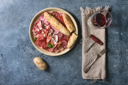 Antipasto meat platter assorti of sliced jamon, salami, chorizo sausage in ceramic plate with bread and glass of red wine on cloth over blue texture background. Flat lay, space