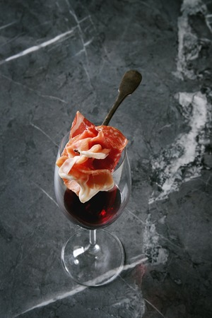 Antipasto meat assorti of sliced jamon, salami, chorizo sausage on fork under glass of red wine over black marble background. High angle view . Appetizer concept