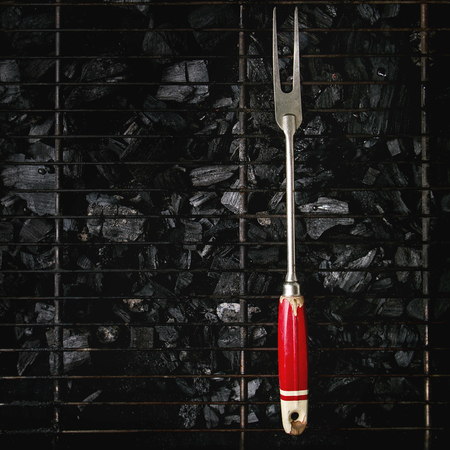 Vintage barbeque fork on bbq grill rack over charcoal. Top view, space. Barbecue concept. Square image