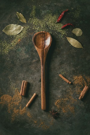 Spices seasoning and herbs variety. Red hot chili chili pepper, bay leaf, cinnamon powder and sticks and empty wooden spoon over dark metal background. Flat lay, space. Cooking concept