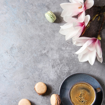 Blue cup of black espresso coffee, french dessert macaroons and spring flowers magnolia branches over grey texture background. Top view, space. Spring greeting card. Square image Stock Photo