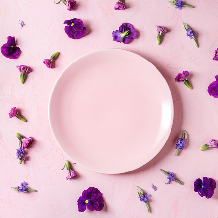 Variety of purple edible flowers for dish decorating with empty ceramic plate over pink pastel background. Top view, space. Square image Archivio Fotografico - 116560209