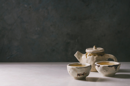 Hot green tea in two traditional chinese clay ceramic cup and teapot standing on white marble table.