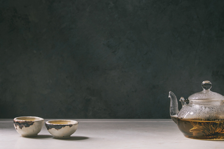 Hot green tea in two traditional chinese clay ceramic cup and glass teapot standing on white marble table. Stock Photo