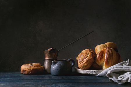 Variety of homemade puff pastry buns cinnamon rolls and croissant served with vintage coffee pot on wooden table. Dark still life. Copy space