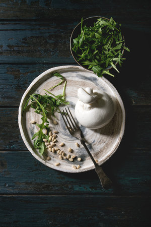 Italian burrata cheese, fresh arugula salad, pine nuts and olive oil in white ceramic plate with fork over dark wooden plank background. Flat lay, space