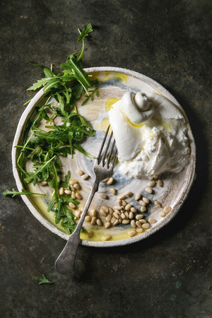 Sliced Italian burrata cheese, fresh arugula salad, pine nuts and olive oil in white ceramic plate over dark metal background. Flat lay, space