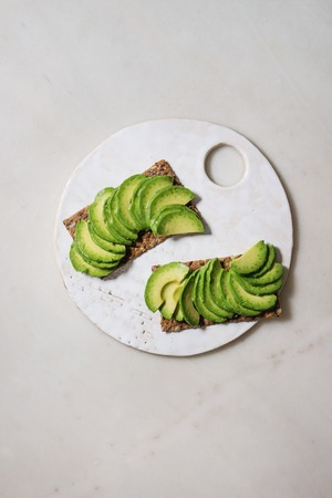 Vegan sandwiches with sliced avocado on rye bread served on ceramic board over white marble background. Flat lay, space