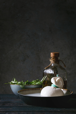 Bowl with whole tied Italian cheese burrata in brine, arugula salad and bottle of olive oil on wooden plank table. Dark rustic style