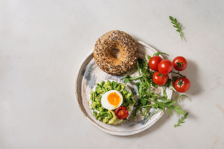 Vegetarian whole grain bagel sandwich with chopped avocado, cream cheese, sun dried tomatoes, egg, arugula served on ceramic plate over white marble background. Flat lay, space