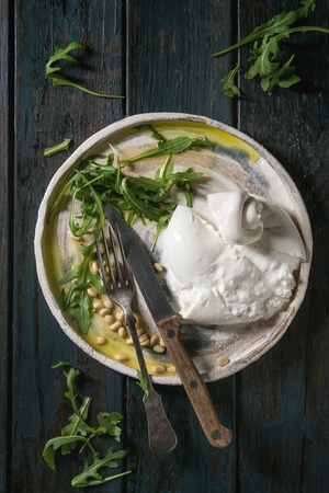 Sliced Italian burrata cheese, fresh arugula salad, pine nuts and olive oil in white ceramic plate on cloth over dark wooden plank background. Flat lay, space