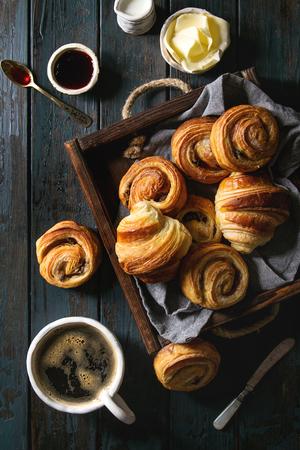 Vielzahl von hausgemachten Blätterteigbrötchen Zimtschnecken und Croissant serviert mit Kaffeetasse, Marmelade, Butter als Frühstück auf dunklem Holzhintergrund. Flache Lage, Raum Standard-Bild