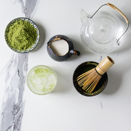 Ingredients for making matcha ice drink. Green tea matcha powder in ceramic bowl, bamboo spoon, whisk, milk, glass teapot, ice cubes over white marble background. Flat lay, space. Square image Stock Photo