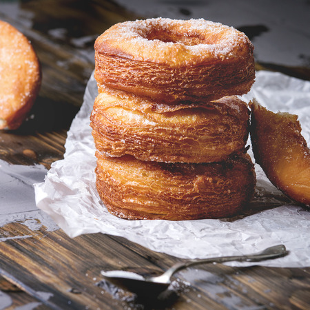 Homemade puff pastry deep fried donuts or cronuts in stack with sugar standing on crumpled paper over dark wooden concrete table. Square image