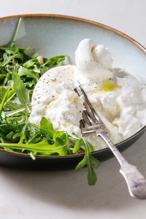 Sliced Italian burrata cheese, fresh arugula salad, pine nuts and olive oil in white ceramic plate on cloth over white marble table. Close up