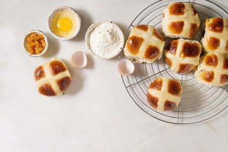 Homemade Easter traditional hot cross buns on cooling rack with ingredients above over white marble background. Top view, space
