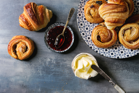Variety of homemade puff pastry buns cinnamon rolls and croissant served with jam, butter as breakfast over blue texture background. Flat lay, space Stock fotó