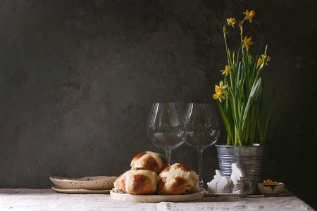 Homemade Easter traditional hot cross buns in ceramic plate standing with narcissus flowers and bunny decor on linen tablecloth. Copy space. Stock Photo