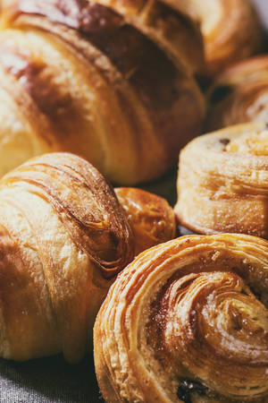 Variety of homemade puff pastry buns cinnamon rolls and croissant. Close up. Foto de archivo