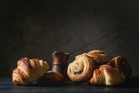 Variété de brioches de pâte feuilletée faites maison, petits pains à la cannelle et croissants servis avec une cafetière vintage sur une table en bois. Nature morte sombre. Espace de copie