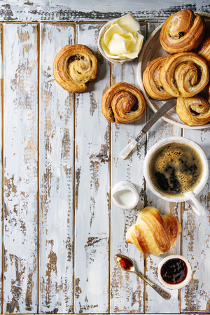 Variety of homemade puff pastry buns cinnamon rolls and croissant served with coffee cup, jam, butter as breakfast over white plank wooden background. Flat lay, space Stock Photo