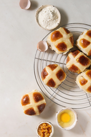 Homemade Easter traditional hot cross buns on cooling rack with ingredients above over white marble background. Top view, space Stock Photo - 116814823