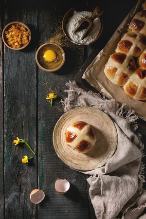 Homemade Easter traditional hot cross buns on plate and oven tray with baking paper and ingredients above over dark wooden background. Top view, space. Rustic style.