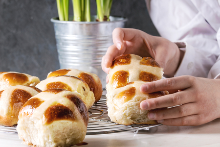 Child hands take homemade Easter traditional hot cross buns on cooling rack on white marble table with narcissus flowers.