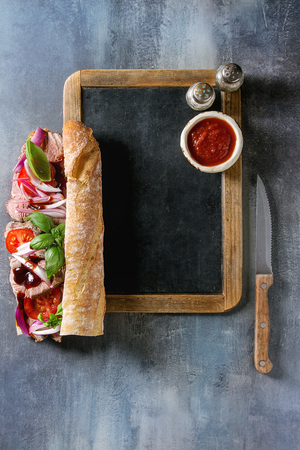 Beef baguette sandwich with tomatoes, basil, red onion served on empty black chalkboard with knife, salt and sauce over blue texture background. Flat lay, space Stock fotó