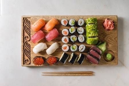 Sushi Set nigiri and sushi rolls on wooden serving board with soy sauce and chopsticks over white marble background. Flat lay, space. Japan menu