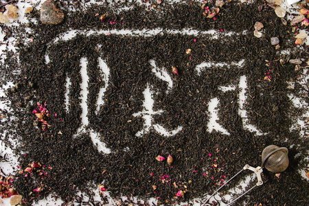 Calligraphic inscription gothic letters tea over dry black ceylon and green tea scattered on white marble with rose buds and stainer. Tea drinking concept background. Top view
