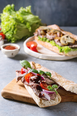Beef baguette sandwich with tomatoes, basil, red onion served on ceramic plate with ingredients above over grey blue table. Stock fotó