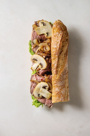 Beef baguette sandwich with champignon mushrooms, green salad, fried onion with ingredients above over white marble background. Flat lay, space Stock fotó