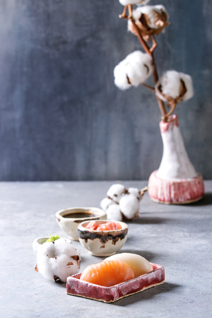 Sushi Set nigiri with salmon and butterfish in pink ceramic serving plate with bowls of soy sauce and pickled ginger, cotton flowers on light blue table. Japan menu Stock Photo