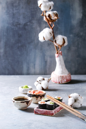 Sushi rolls set in pink ceramic serving plate with chopsticks, bowls of soy sauce, and pickled ginger, cotton flowers on light blue table. Japan menu. Copy space