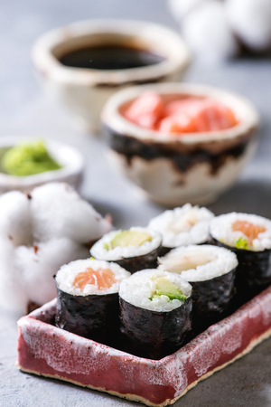 Sushi rolls set in pink ceramic serving plate with bowls of soy sauce and pickled ginger, cotton flowers on light blue table. Japan menu. Close up Stock Photo