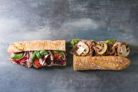 Two Beef baguette sandwiches with champignon mushrooms, green salad, fried onion, tomatoes over blue texture background. Flat lay, space