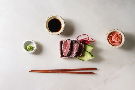 Tuna Sushi sashimi with cucumber in pink ceramic serving plate with chopsticks, bowls of soy sauce, and pickled ginger, cotton flowers over white marble background. Flat lay, space. Japan menu Stock Photo