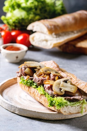 Beef baguette sandwich with champignon mushrooms, green salad, fried onion served on ceramic plate with ingredients above over grey blue table. Close up.