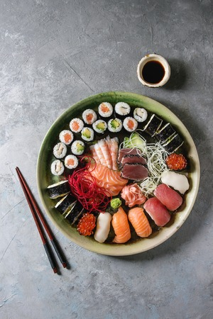Sushi Set nigiri sashimi and sushi rolls in ceramic serving plate with salad, soy sauce and chopsticks over grey concrete background. Flat lay, space. Japan menu
