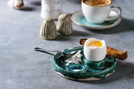 Breakfast with cup of coffee and soft boiled egg, served in green ceramic egg cup with salt, pepper and toasted bread, jug of cream over grey blue table. Archivio Fotografico - 118584783